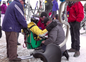 Volunteers help a disabled skier into a specially designed piece of equipment during the annual Ski for Light event at Terry Peak Wednesday. Photo Date: Jan. 23, 2019.