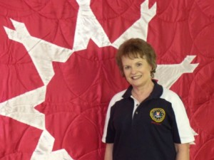 Gayle Thom in front of tribal flag