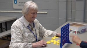 Dorothy Larsh plays Connect 4 at Club for Boys