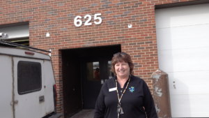 Jeanne at the entrance of building that houses the store